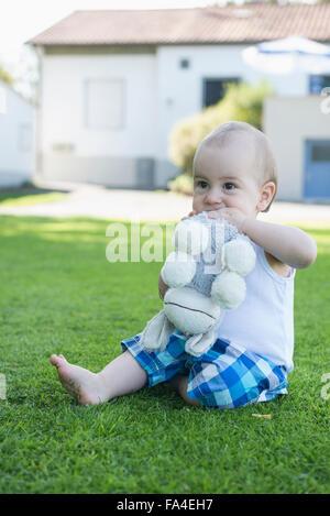 Cute little baby boy biting donkey toy in the garden, Munich, Bavaria, Germany - Stock Photo