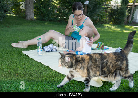 Mother feeding her baby boy with bottle in lawn and cat walking across, Munich, Bavaria, Germany