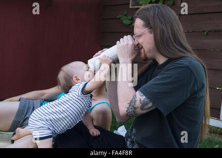 Baby boy and his father looking through a roll of paper towels from both ends, Munich, Bavaria, Germany - Stock Photo