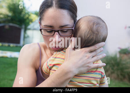 Mother comfort her baby son in a lawn, Munich, Bavaria, Germany - Stock Photo