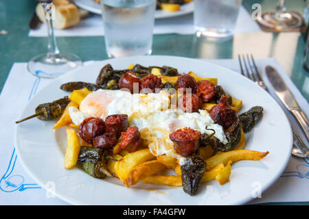 Fried eggs with chorizo, Padron peppers and chips. - Stock Photo