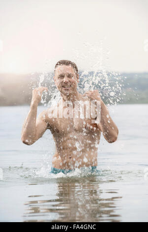 Mature man in lake with full of splash, Bavaria, Germany - Stock Photo
