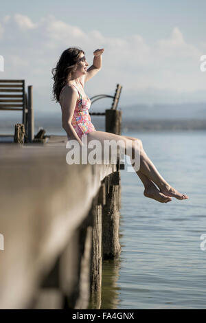Mature woman sitting in swimsuit on pier and looking at distance, Bavaria, Germany - Stock Photo