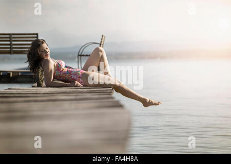 Mature woman lying in swimsuit on pier, Bavaria, Germany - Stock Photo