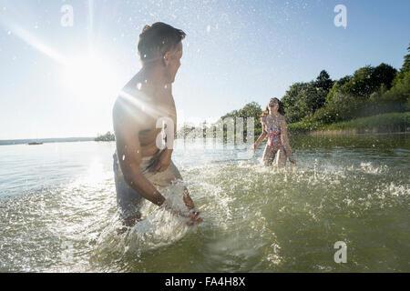 Mature couple splashing water to each other on lake, Bavaria, Germany - Stock Photo
