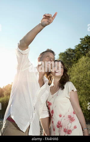 Mature man showing something to his wife at lakeside, Bavaria, Germany - Stock Photo