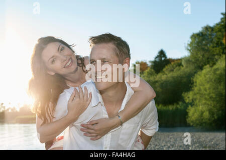 Mature man giving piggyback ride to his wife at lakeside, Bavaria, Germany - Stock Photo