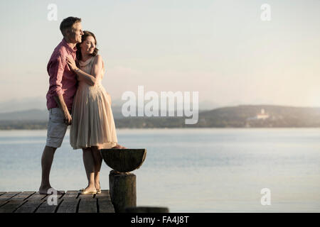 Mature couple standing on pier and looking over lake, Bavaria, Germany - Stock Photo