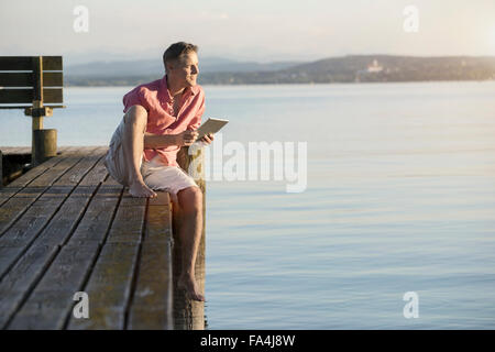 Mature man using digital tablet on pier and looking over lake, Bavaria, Germany - Stock Photo