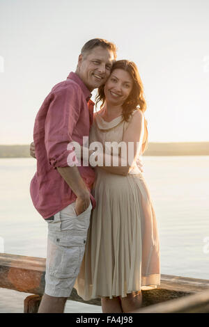 Portrait of mature couple smiling on pier at lake, Bavaria, Germany - Stock Photo