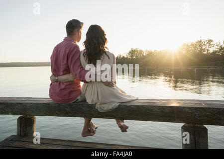 Mature couple sitting on pier looking at sunset, Bavaria, Germany - Stock Photo