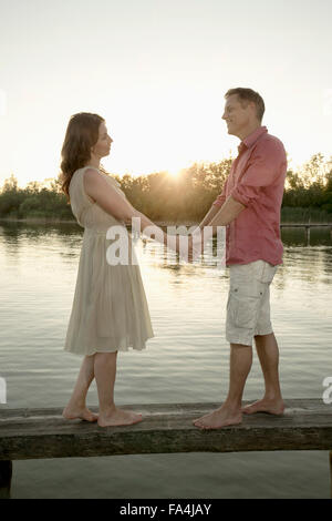 Mature couple standing with holding hands on pier at lake during sunset, Bavaria, Germany - Stock Photo
