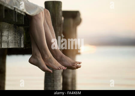 Couple legs dangling on pier, Bavaria, Germany - Stock Photo