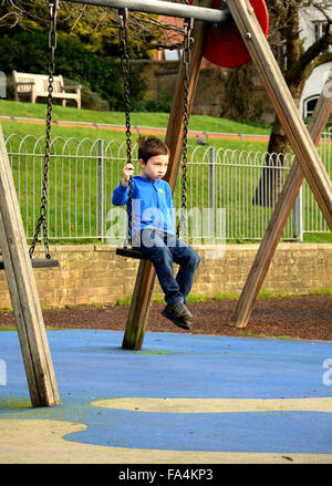 A boy in a blue jacket sits on a swing in a children's playground. - Stock Photo