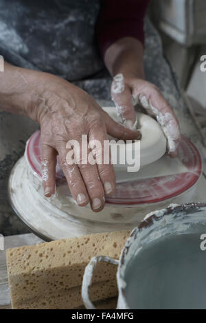 Close-up of female potter moulding clay in workshop, Bavaria, Germany - Stock Photo