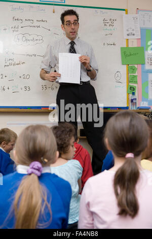 Teacher standing in front of whiteboard talking to group of school children, - Stock Photo