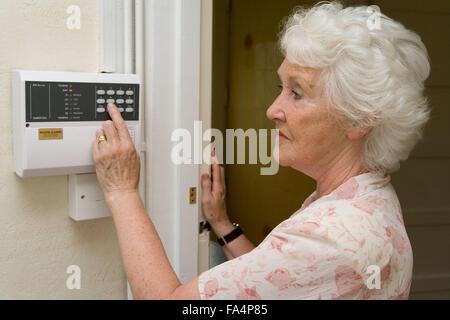 Woman setting house alarm system, - Stock Photo