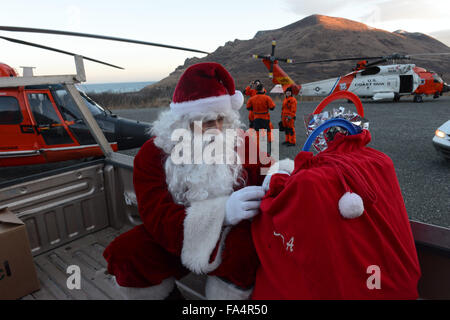 Santa Claus prepares his bag of presents after arriving to visit children in remote villages with the assistance - Stock Photo