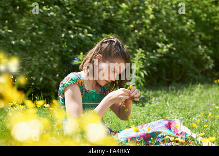 Girl making floral crown in park, Munich, Bavaria, Germany - Stock Photo