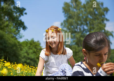 Girl making floral crown with her friend wearing floral crown in park, Munich, Bavaria, Germany - Stock Photo