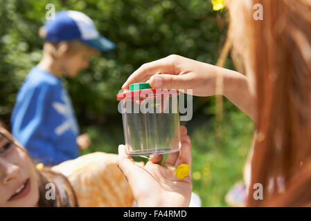 Girls examining a spider in container, Munich, Bavaria, Germany - Stock Photo
