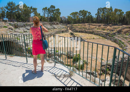Woman tourist solo, rear view of a mature female tourist taking a photo of the Roman amphitheatre ruins in the Archaeological - Stock Photo