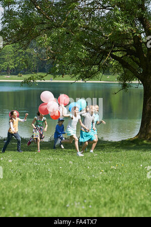 Children running in park with balloons, Munich, Bavaria, Germany - Stock Photo
