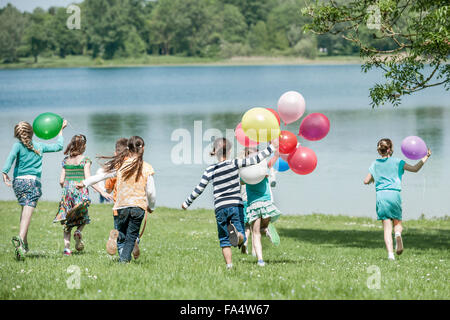 Rear view of children running in park with balloons, Munich, Bavaria, Germany - Stock Photo