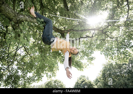 Girl hanging on tree and smiling, Munich, Bavaria, Germany - Stock Photo