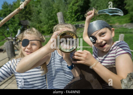 Three girls playing on a pirate ship in adventure playground, Bavaria, Germany - Stock Photo