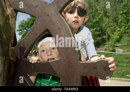 Two boys peeking from rudder of a pirate ship in adventure playground, Bavaria, Germany - Stock Photo