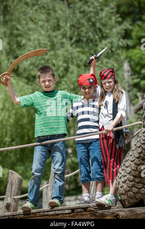 Three friends dressed up as pirates playing on pirate ship in adventure playground, Bavaria, Germany - Stock Photo