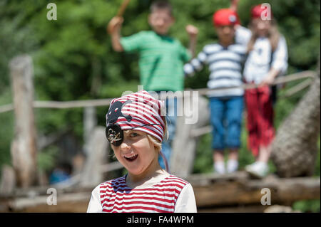 Boy dressed up as a pirate playing in adventure playground with his friends in the background, Bavaria, Germany - Stock Photo