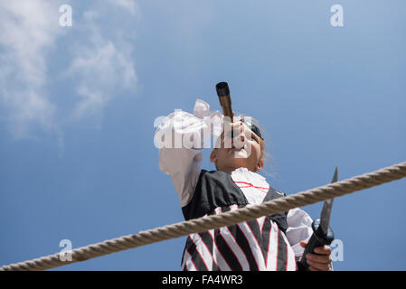 Girl looking through telescope in playground, Bavaria, Germany - Stock Photo