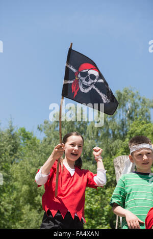 Girl holding pirate flag with her friend in adventure playground, Bavaria, Germany - Stock Photo