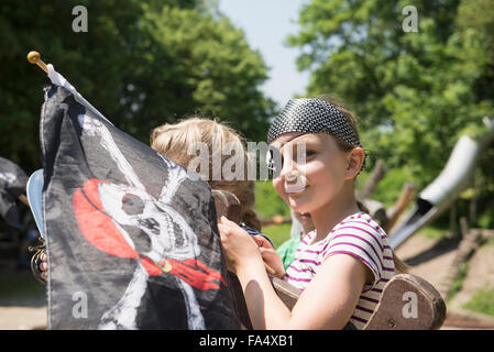 Portrait of a girl dressed up as a pirate holding pirate flag in adventure playground, Bavaria, Germany - Stock Photo