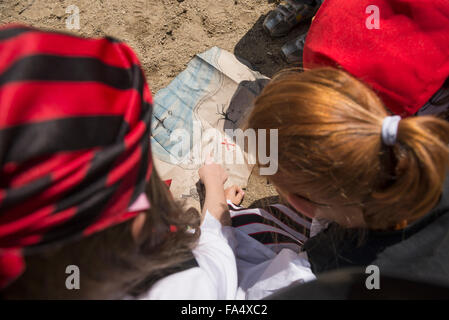Girls examining a treasure map in a adventure playground, Bavaria, Germany - Stock Photo
