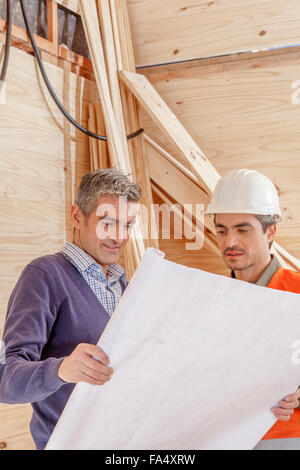 Builder On Building Site Looking At Plans With Apprentices - Stock Photo