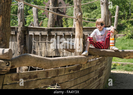 Boy sitting on pirate play ship in adventure playground, Bavaria, Germany - Stock Photo