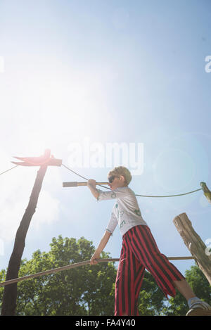 Boy standing on pirate ship in playground and looking through telescope, Bavaria, Germany - Stock Photo