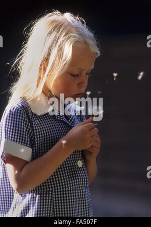 Young girl blowing dandelion seeds and making a wish. - Stock Photo