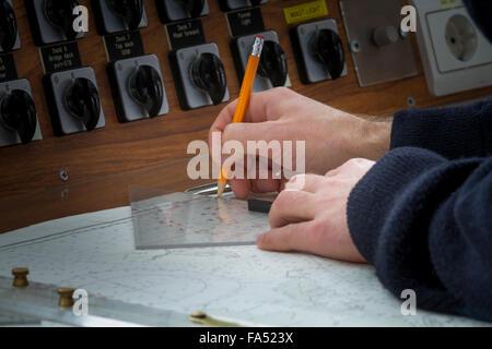 Captain checking charts on ship's bridge, close up, Antarctica - Stock Photo