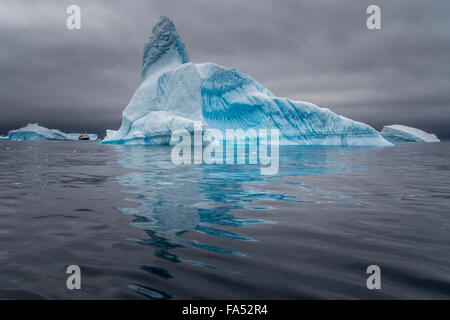 Huge iceberg with a cruise ship for size comparison, set off vibrantly against the moody sky, Antarctica - Stock Photo