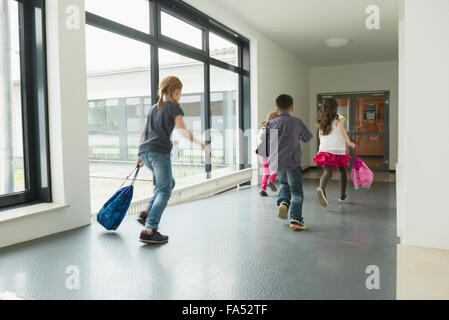 Children running with sports bags in corridor of sports hall, Munich, Bavaria, Germany - Stock Photo