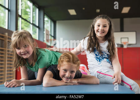 Girls resting on exercise mat in sports hall, Bavaria, Munich, Germany