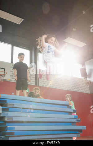Children jumping from stack of sport mats in sports hall, Munich, Bavaria, Germany - Stock Photo