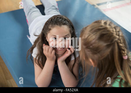 Girl lying on exercise mat in sports hall, Bavaria, Munich, Germany - Stock Photo