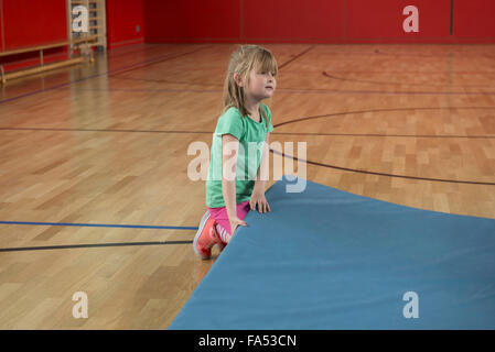 Child Girl Does Gymnastics Sitting In Butterfly Pose