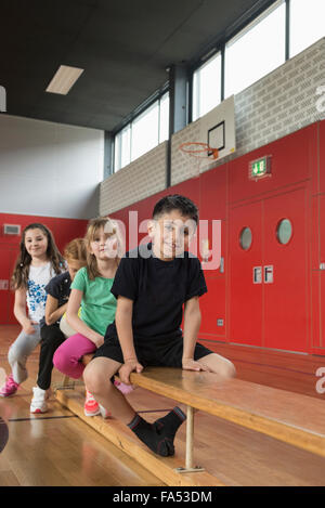 Children sitting on bench in sports hall, Bavaria, Munich, Germany - Stock Photo