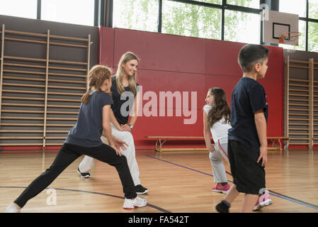 Teacher doing extension exercise with school children in sports hall, Munich, Bavaria, Germany - Stock Photo
